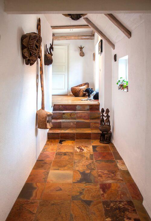 I den smala hallen utanför sovrummet känns det ett tag som du är i Afrika. Mustigt bruna toner kombinerat med vitt och genuina detaljer som är inropade på olika auktioner. Hunden Boss ligger och vaktar.
