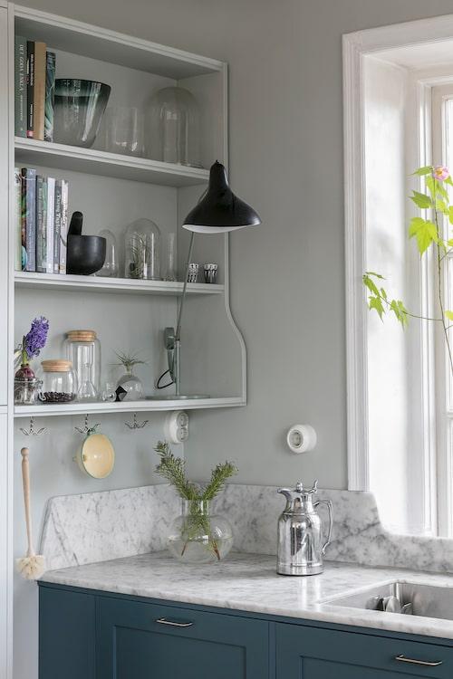 Bänkskivor i carraramarmor från Höörs marmor & granit. Svart lampa från Bernard Schottlander.