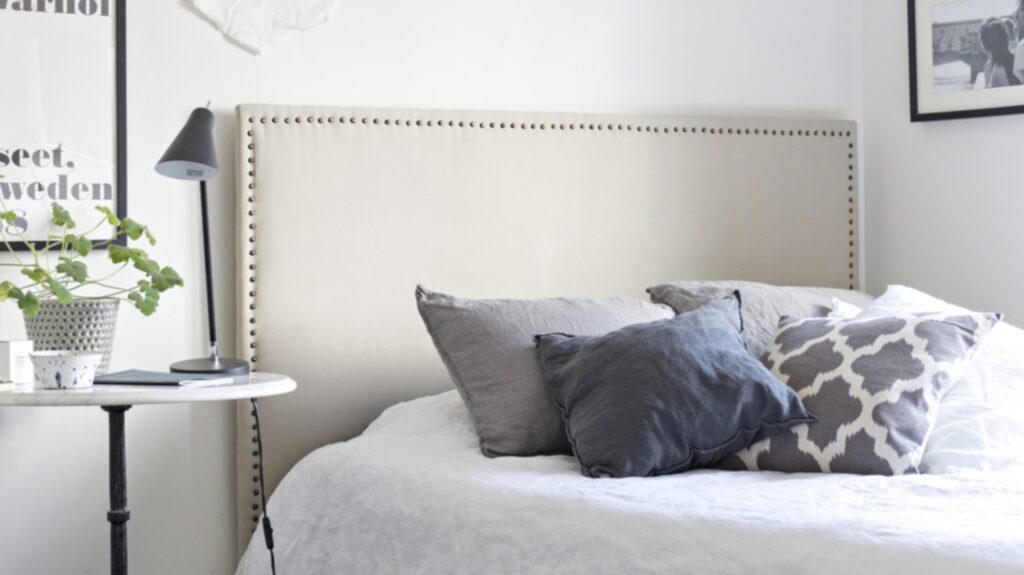 Sovrum. Sänggaveln har Frida tillverkat själv av en skiva som klätts med tyg och som sedan har fått möbelnitar längs kanterna. Även vimpeln på väggen är ett hemmapyssel ett resultat av Fridas kreativa idéer.