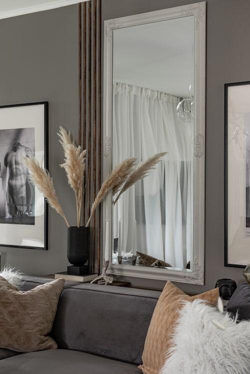 På väggen intill spegeln har Josefin och Lenny satt upp vanliga täcklister som en personlig väggdekoration. Soffa, Soffadirekt.