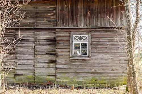 Ladan är i behov av renovering. Här inne står många gamla möbler, en nedmonterad kakelugn, flera spegeldörrar och fönster.