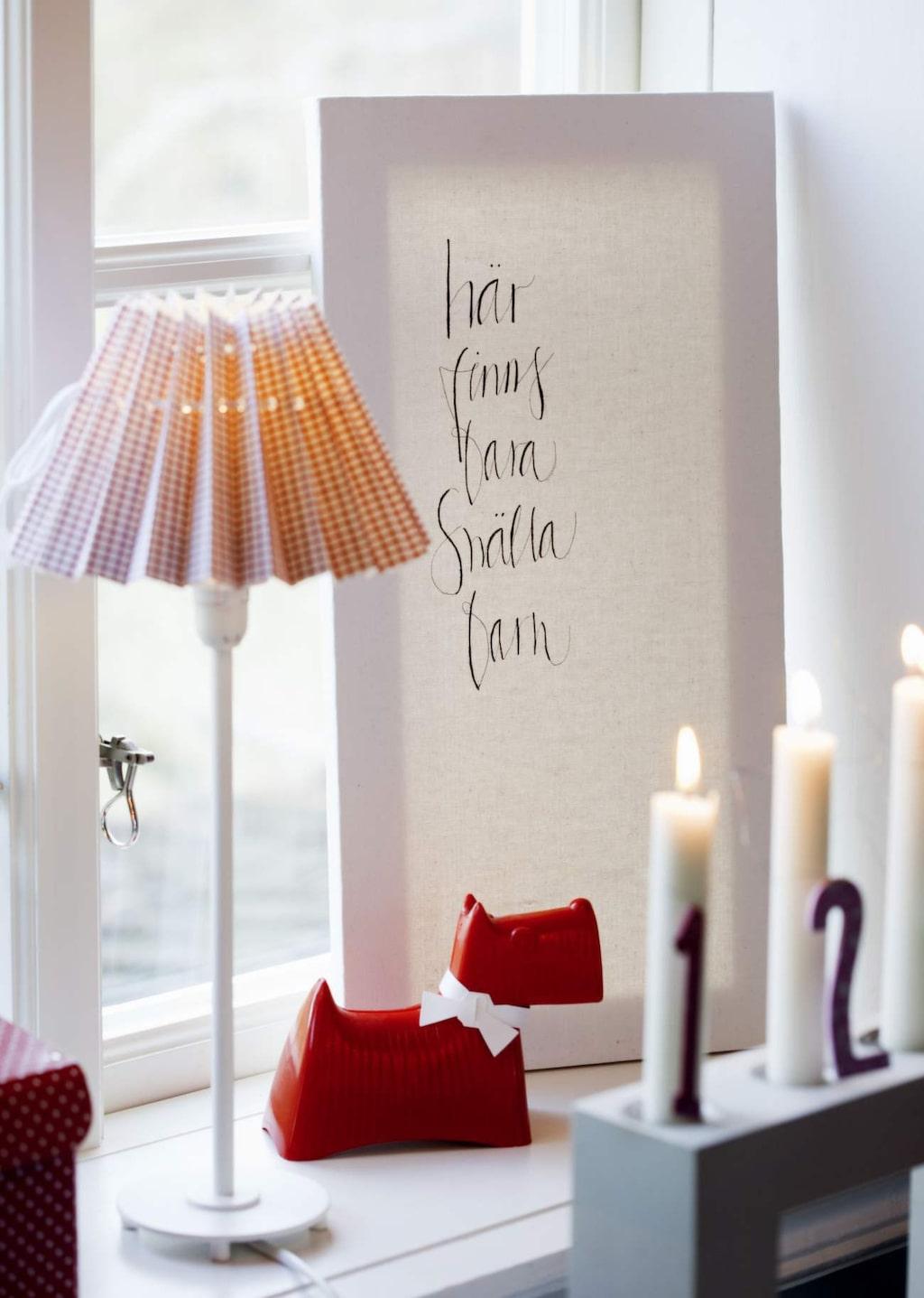 I fönstret står en kalligrafitavla från Ylva Skarp.