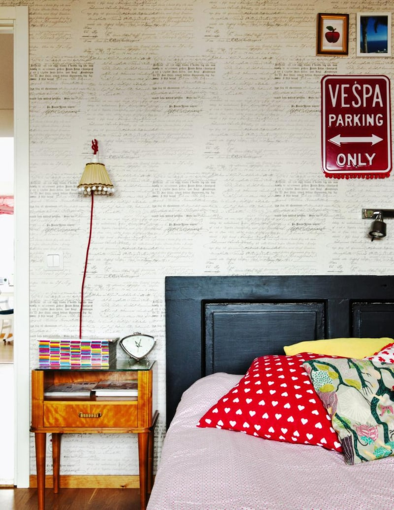 """Dörr som gavel. Tuff stilbrytning i sovrummet med gammal svartmålad dörr som sänggavel, nattduksbord i retrostil och gammeldags lampa med bollfrans och knallröd textilsladd. Tapeten med skrivstilstext kommer från Boråstapeter och kollektionen """"Vintage""""."""