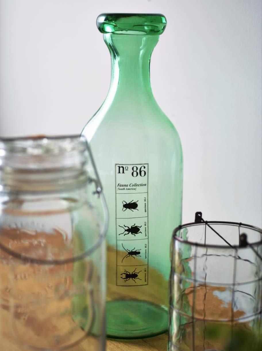 Härliga detaljer i glas. Inred med vackra glasflaskor och liknande. Damejeannen syns ofta i inredningssammanhang. Här dekorerade vi en grön flaska, 899 kronor, House doctor. Flaska i glas med kran, 249 kronor, Åhléns. Lykta, 149 kronor, Indiska.