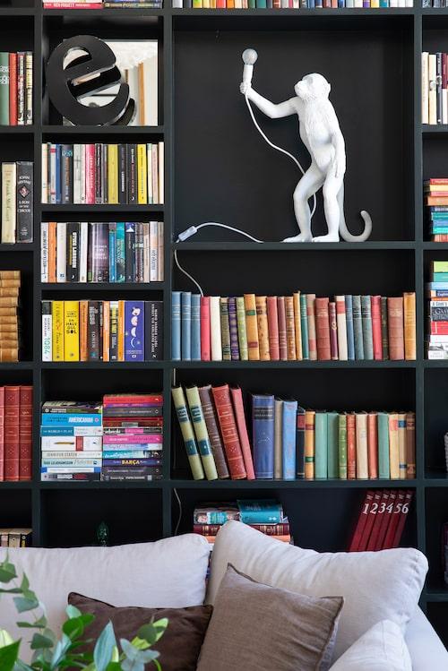 Den snygga bokhyllan har paret platsbyggt och målat själv. Vit aplampa i bokhyllan, Seletti.
