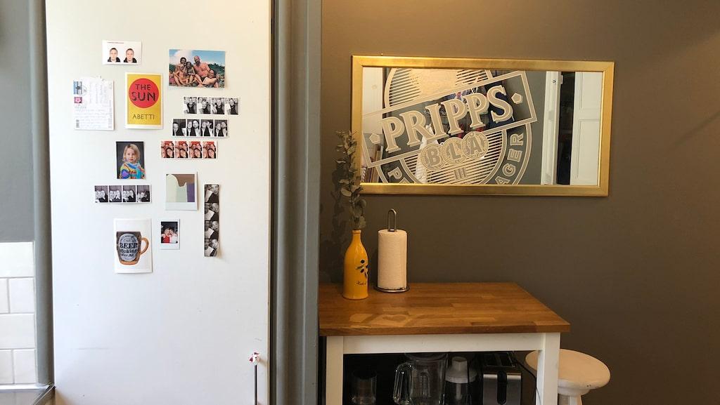 På kylskåpet sitter fotografier och bredvid står en liten köksö som fick flytta på sig när...
