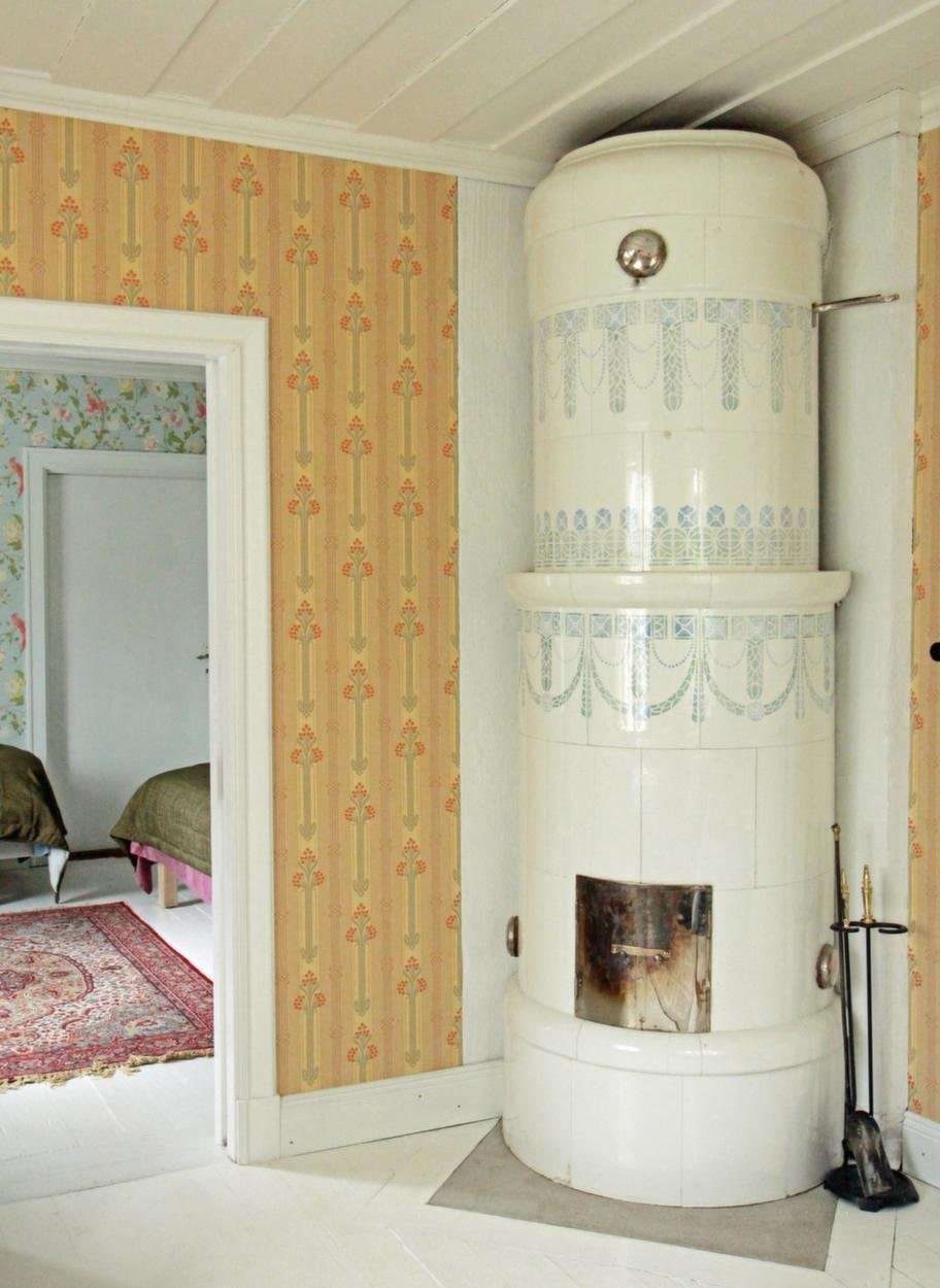 Klassisk kakelugn<br>Alla rum i Bagarstugan har nygamla tapeter. Den gula tapeten kommer från Duros gammelsvenska kollektion.