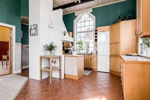 När du står och diskar i köket kan du titta ut genom de stora spröjsade fönstret.