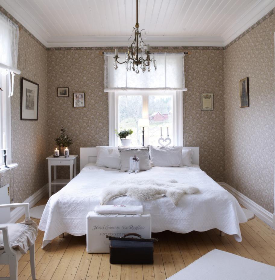 Mjuka färger. Sovrummet är en romantisk dröm med vackra allmogetapeter på väggarna. Som sänggavel har paret en gammal dörr.