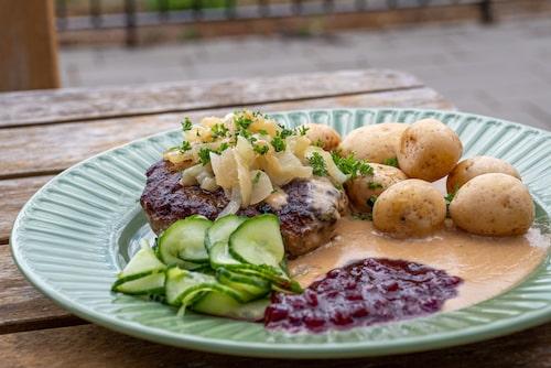 Café Doppingens paradrätt - pannbiff med gräddsås, lingonsylt, pressgurka, kokt potatis och stekt lök.