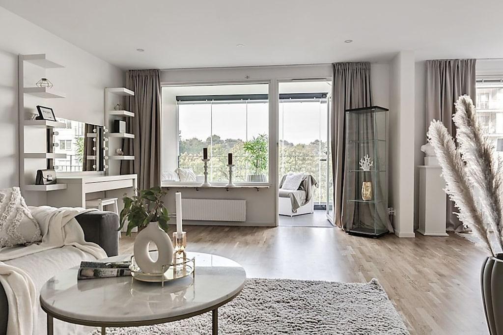 Vardagsrummet har stora fönster i västerläge och utgång till en inglasad balkong.