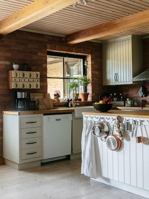 Köket är målat i en lindblomsgrön kulör. På väggarna sitter skivor klädda med tegelfasader. Kökshanddukarna vävde Davids farmor när hon var ung.