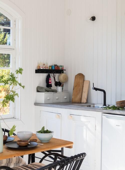 Köksinredningen bygger på två skåpsstommar från Ikea som klätts med pärlspont. Dörrarna har sågats till av en gammal spegeldörr. Bänkskivan är gjuten i betong.