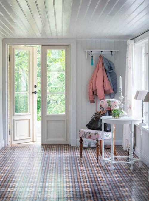 Den rymliga hallen har ett vackert mönstrat golv. Den gamla stolen är klädd med mönstrad fransk textil som Catherine låtit klä om. Det runda lilla bordet är ett loppisfynd. Golv fån Stiltje.