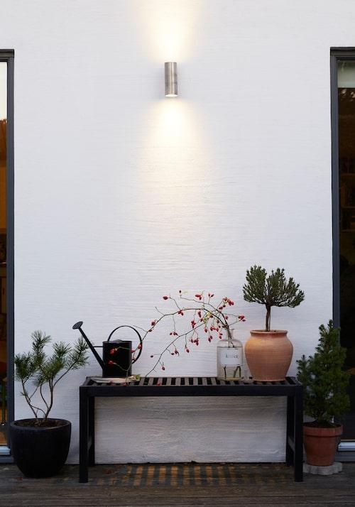 Under en stilren spotlight på väggen står ett av Annas vackra trädgårdsstilleben.