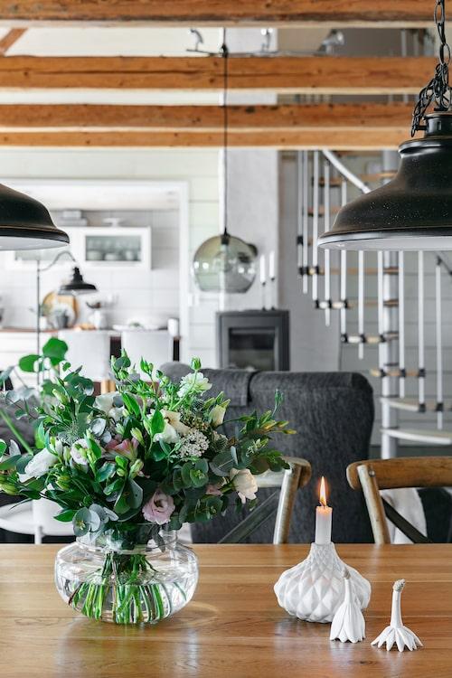 På matbordet står en vacker bukett som Lina Gunnarsson på Blomsterverkstan i Höör bundit. Bredvid står en ljusstake inköpt på Blomsterverkstan. Keramikblommor från Madam Stoltz.