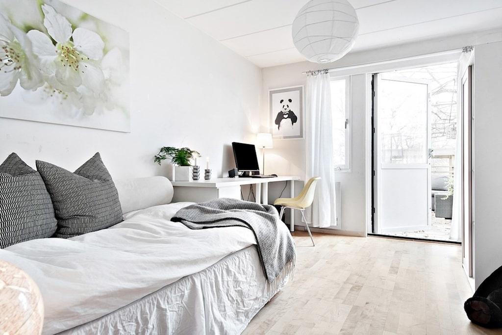 Ett av två sovrum på nedre plan, med utgång till altan. Plats för dubbelsäng och tillhörande möblemang. Garderober som sväljer allt och ett mörkare laminatgolv.