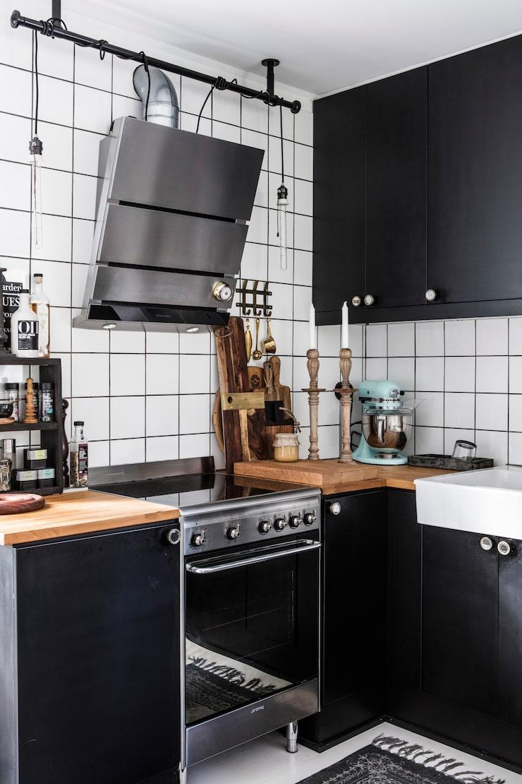 Köket är ursprungligen ett vitt Ikeakök som paret lackat om i mattsvart och bytt handtag. Egentillverkad taklama i industristil. Fläkt från Electrolux och spis från Smeg. Skärbrädor från Nicolas Vahe, Jamie Oliver och Indiska.