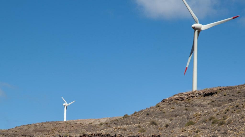 Gammalt möter nytt: gunachegravar i Agaetedalen där bergen krönts med vindkraftverk.