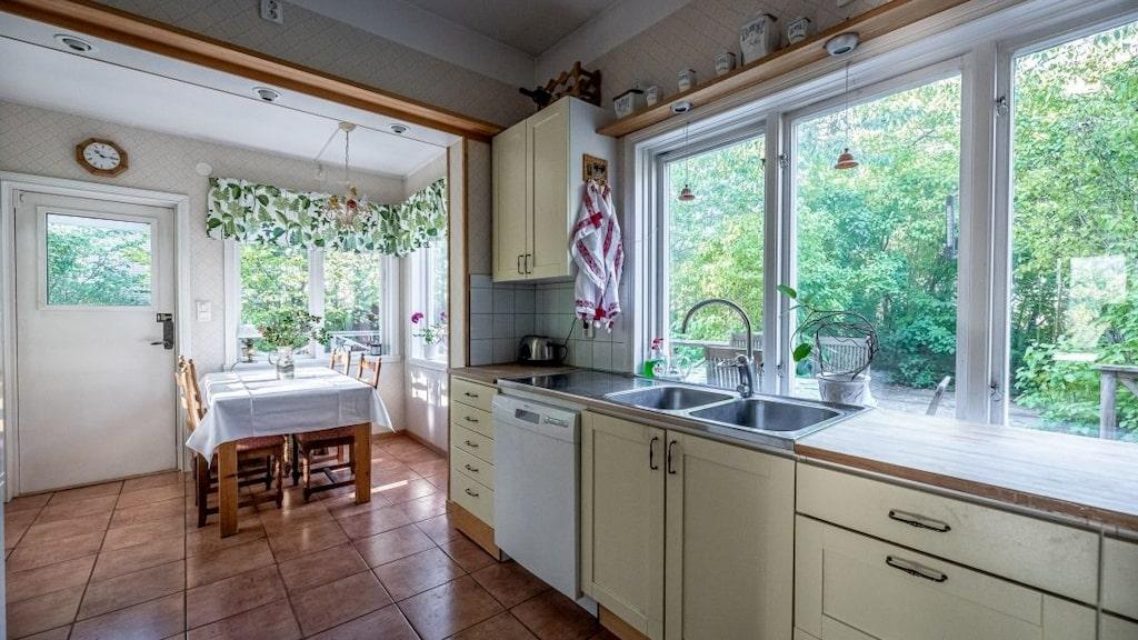 Kök med matplats och härliga fönster över arbetstbänken.