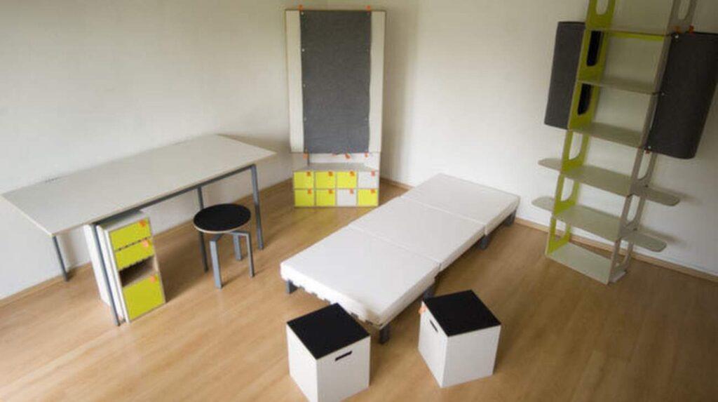 Säng med madrass, skrivbord, lådhurts, garderob, bokhylla, stol och två pallar.