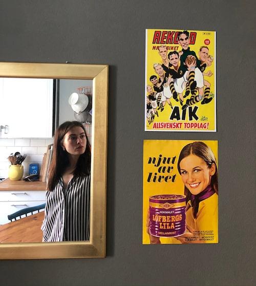 Sofia och köket i spegelbilden och gamla affischer på väggen.