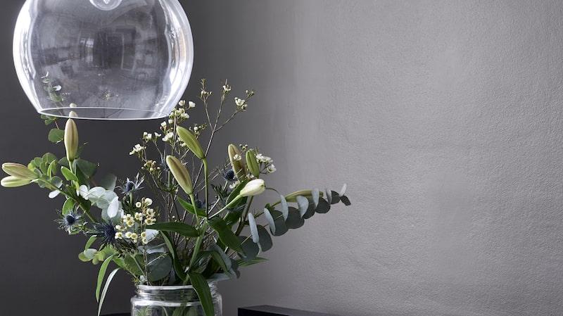 På köksbordet står en glasburk från Lagerhaus med en blandbukett bestående av liljor i knopp, vaxblomma och eucalyptuskvistar. Lampa, Ebb & flow, Ljusbox, Bxxlght.