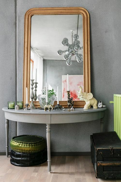 Ett ommålat bord med en stor guldspegel utgör ett vackert blickfång i vardagsrummet. Gröna ljuslyktor, från Olsson & Jensen. Puffar från Strega och Casa Marrakech.