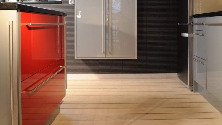 Ett separat väggskåp ger bra förvaring. Taket är sänkt med hjälp av en träpanel som matchar golvet.