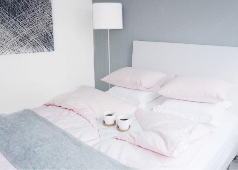 Sovrum. Bäddat med vita och ljust rosa lakan mot en gråmålad vägg.