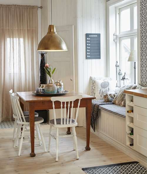 Bordet har tillhört förre ägaren och stod i uthuset. Stolarna är ett kärt arvegods som har hängt med sedan Malins mormor och morfar gifte sig. Lampan är från Ikea och har sprayats med guldfärg. På väggen hänger en veckokalender från Ib Laursen.