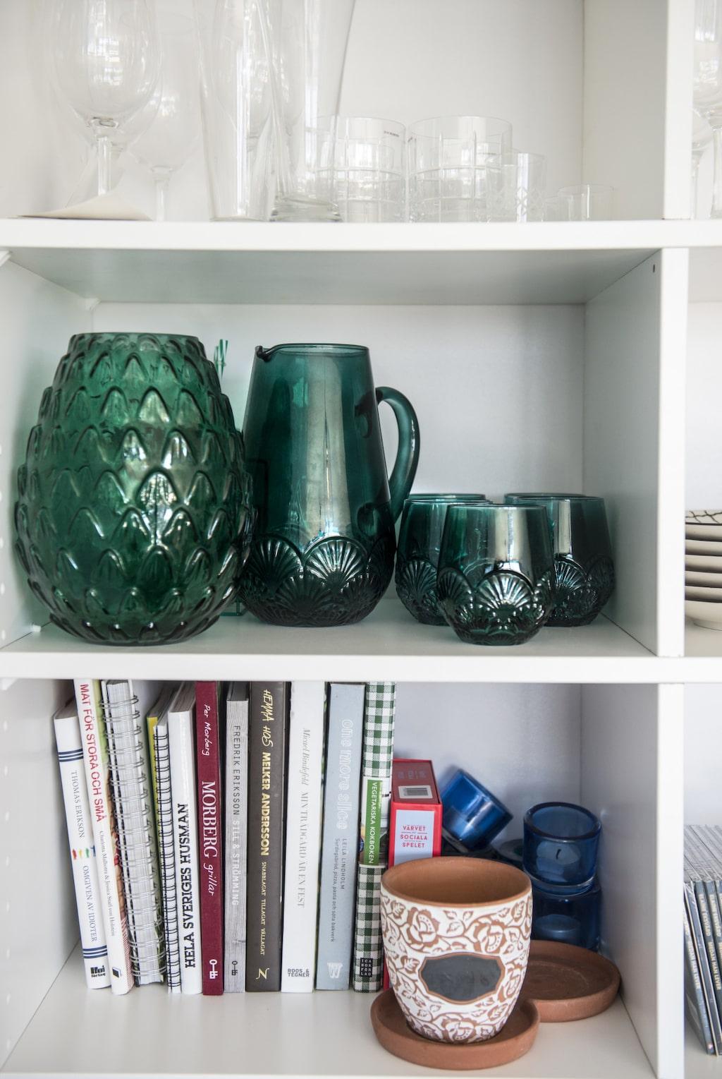 Detaljer. I de öppna hyllorna får porslinet synas. Gröna glas och kanna från H&M home. Kruka från Indiska.