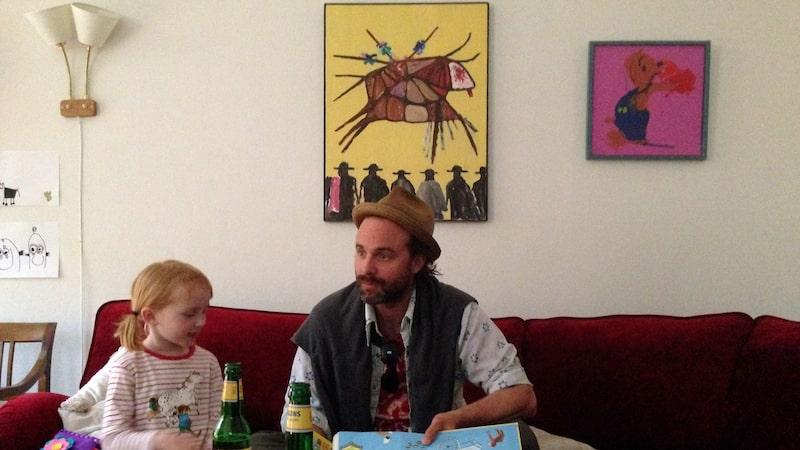 """Skådespelaren och filmproducenten Schiaffino Musarra läser för Ellen Sarri Littorin i vardagsrummet innan det byggdes om till kök. Tavlan """"Bamse"""" har Ellen gjort på förskolan. Olles pappa Lasse Sarri har målat """"Bögarna och döden"""", en tjurfäktning med homosexuella matadorer. Oljemålningen är en av Olles favoriter."""