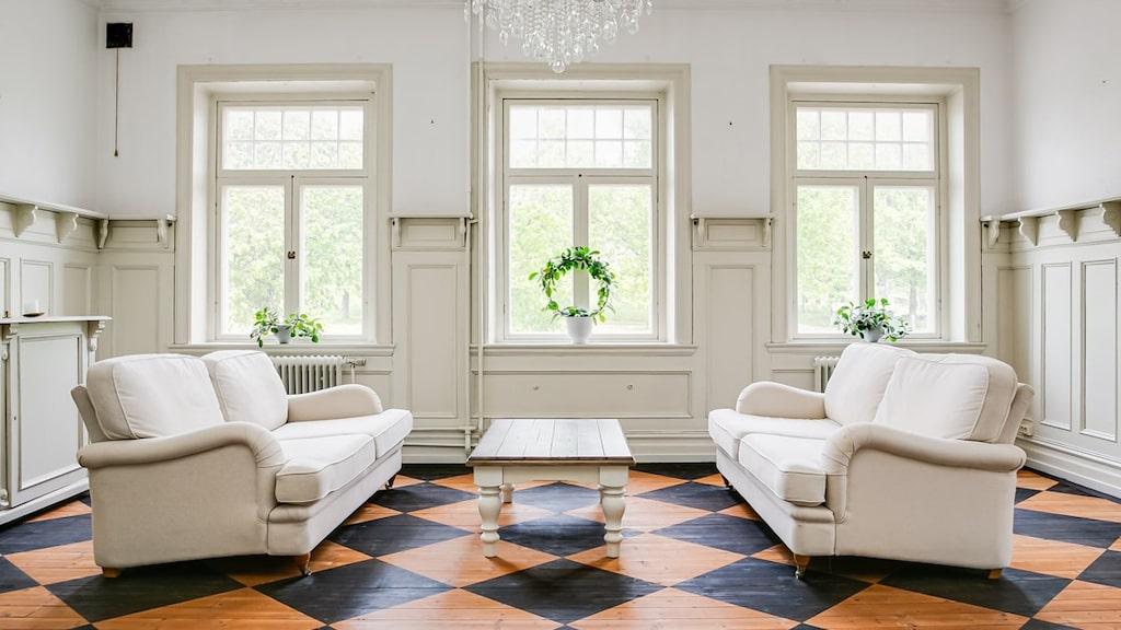 Vardagsrummet med trägolv i schackmönster, bröstpanel och målade väggar. Stora fönster som ger vackert ljus i rummet.
