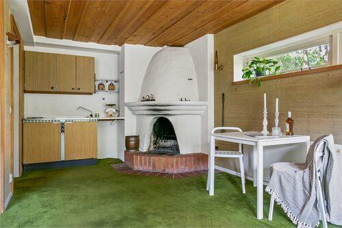 På bottenvåningen finns ytterligare en öppen spis i det kombinerade kök och vardagsrummet.