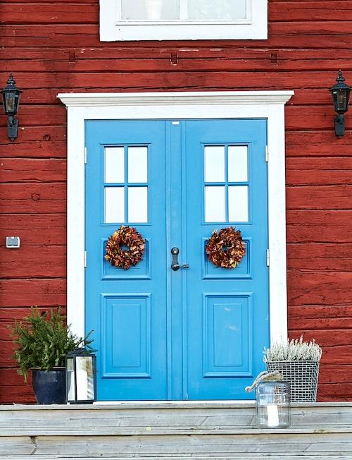 Vid den blå entrédörren till gården i Järvsö välkomnas man av Claras höstfina kransar. Stålkorg, från Korbo.