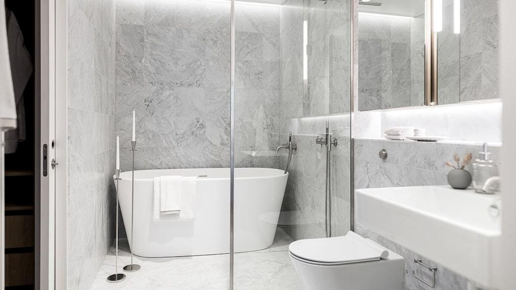 Badrum med väggar och golv i Carraramarmor.