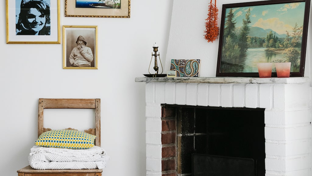 Den öppna spisen används flitigt, då familjen gärna besöker stugan även under vinterhalvåret. På väggen sitter tavlor med havs- och sommartema. Allt köpt på loppis förutom bilden av Jackie Onassis som är köpt på Louisiana i Danmark. Marockanska plattor på golv och spiselkrans kommer från Sidsid, ljuskopparna från Notre Dame i Köpenhamn. På spjällhandtaget hänger ett halsband köpt i Nice för ändamålet.