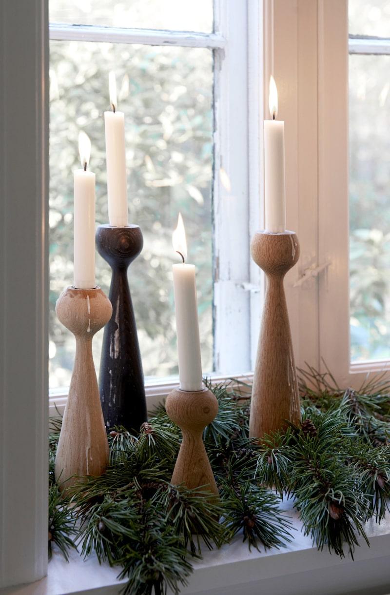 Söta ljusstakar grupperade i granris i fönstret.
