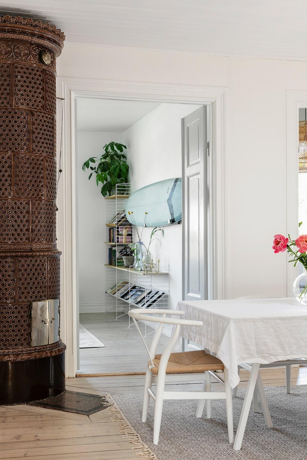 Huset har fyra kakelugnar. I dag fungerar bara en av dem men planen är att dra i gång samtliga, inte minst för att få värme i det 240 kvadratmeter stora huset. Matplatsen har placerats i den rymliga hallen, i anslutning till köket och det vardagsrum som används mest. Där skymtar spår av ett av Nils stora intressen: surfing. Matsalsbordet kommer från Hay, stolarna från Voga.