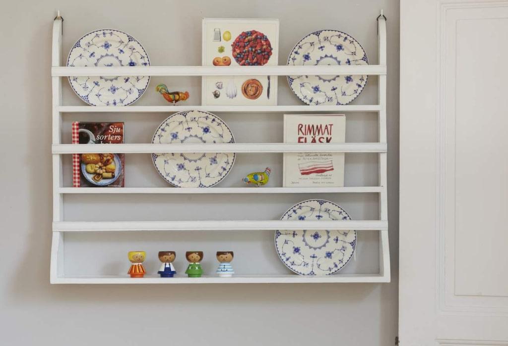 På tallrikshyllan i köket samsas Cecilias ärvda tallrikar med loppisfynd och favoritkokböcker.