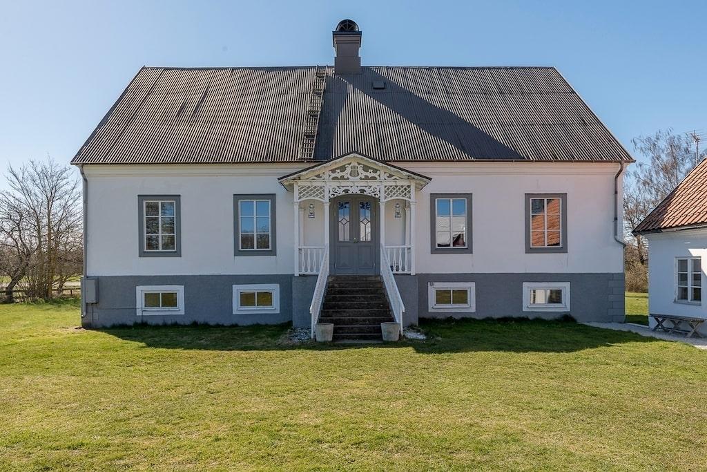 Denna vackra bostad nås via huvudingång mot gårdsplanen. Precis utanför entréns pampiga pardörrar finns sittplatser på verandan.