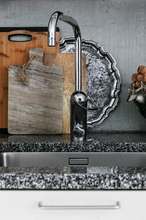 Bakom kranen i köket står olika skärbrädor och brickor samlade.