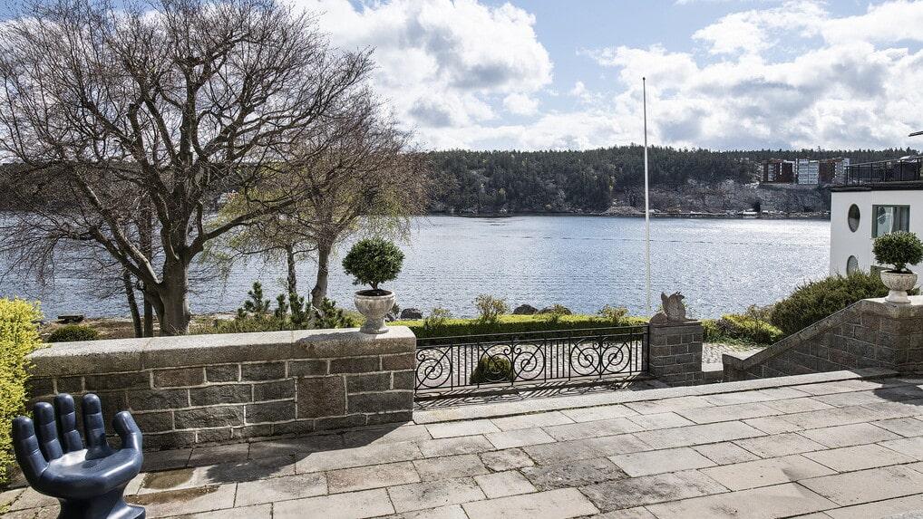 Fri utsikt över vattnet och den välskötta trädgården med flera uteplatser, klipphällar samt brygga.