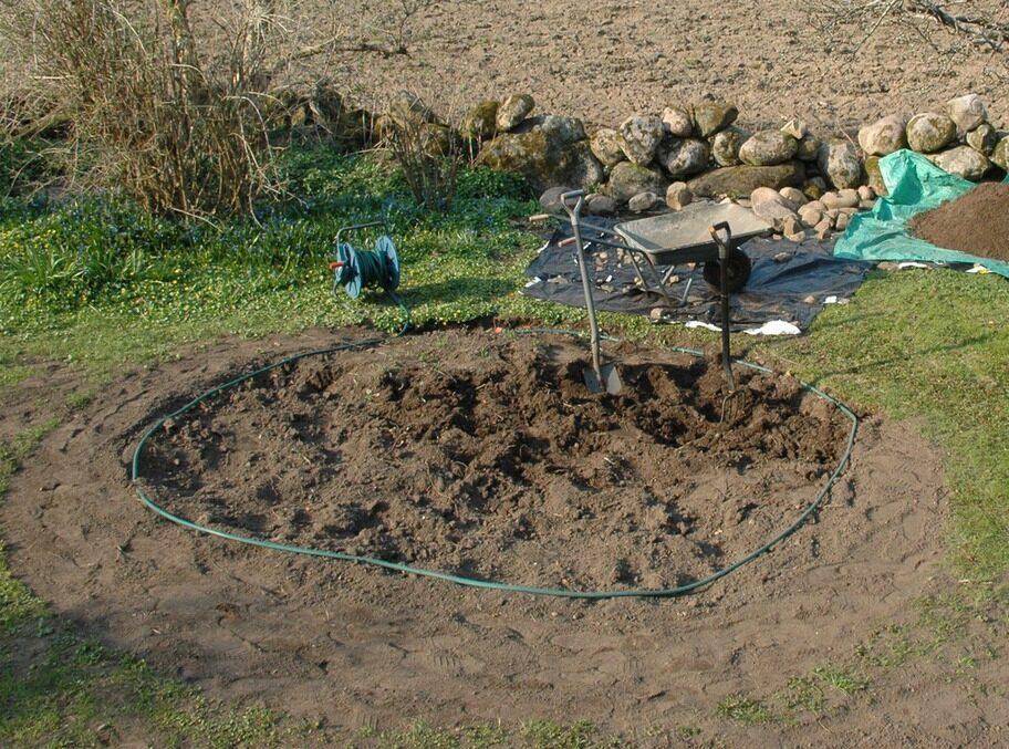 """1. MÄT UT Vi la ut en trädgårdsslang för att markera storleken på dammen. Ungefär 3,5 meter tvärs över verkade bra. Det skulle också bli någon form av ett litet vattenfall med en pump i dammen, därför passade det bra att lägga upp """"schaktmassorna"""" vid sidan om. En blomsterklädd kulle skulle dölja den risiga muren mot åkern bakom. Högst upp på kullen skulle det finnas ett kar med en mindre vattenspegel. Därifrån ska vattenfallet komma porlande, berättar Björn."""