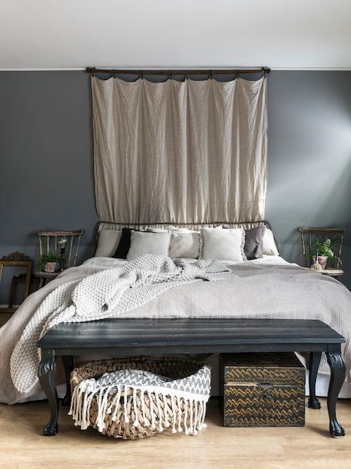 Emma har tillverkat sänggaveln av en gammal gardinstång i trä, två hopsydda gardiner och ett flätat läderband som är köpt på loppis. Bänken har Emma byggt av frambenen från två gamla stolar.