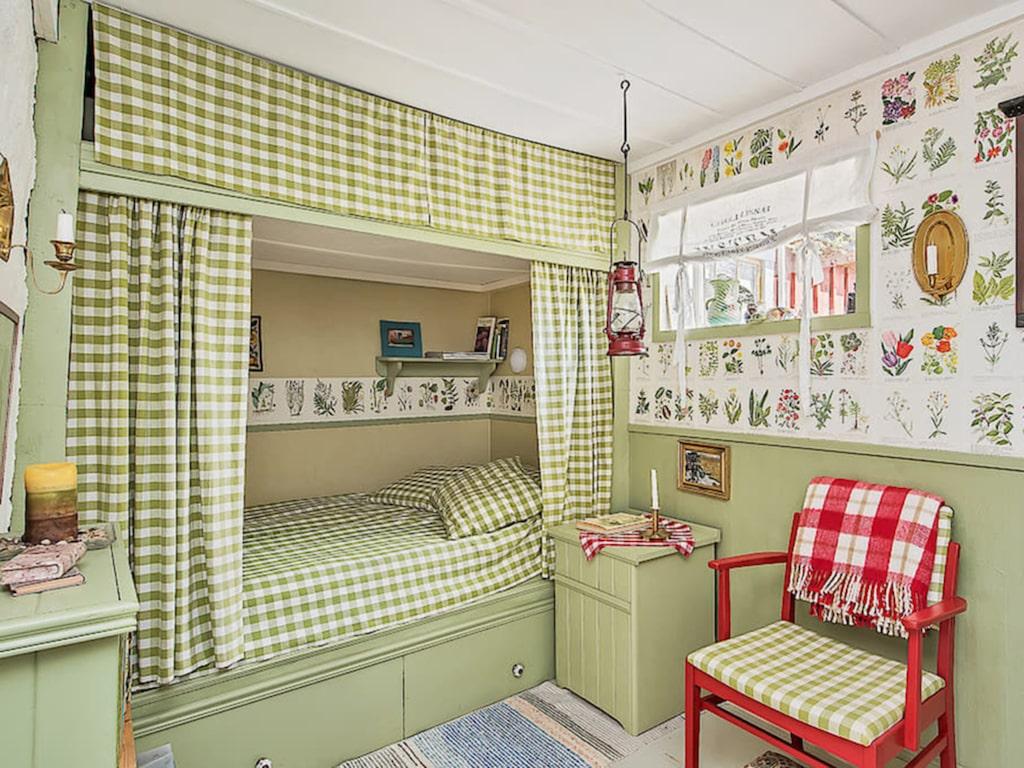 I sovrummet finns en platsbyggd säng som har förvaring både ovan och under med tyg framför som matchar med den härliga gröna färgen som både väggar och säng har.
