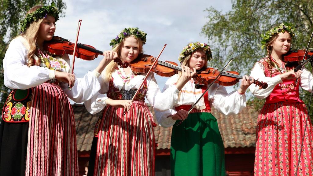 Blomsterkrans i håret, folkdräkt och fiol – så firar man midsommar i Dalarna.