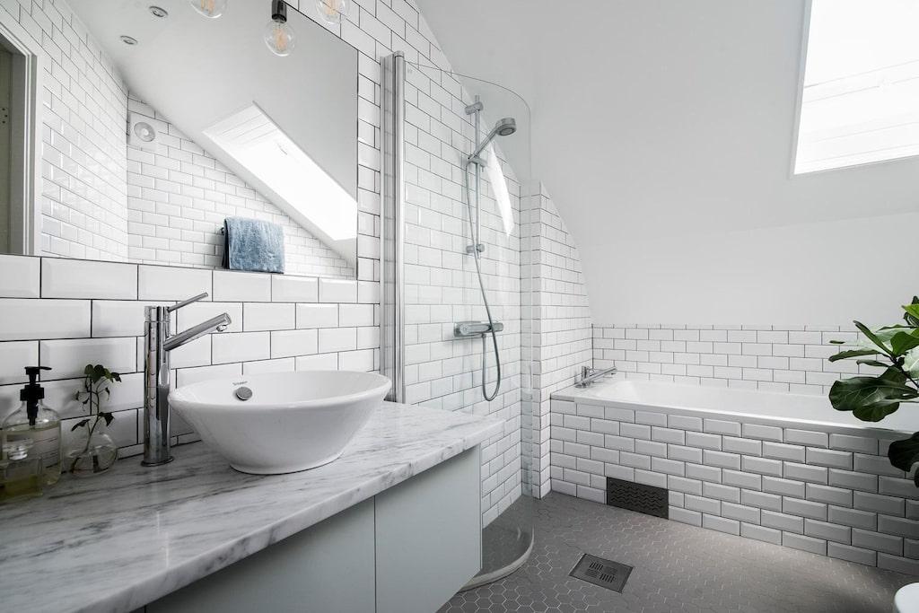 Påkostat och smakfullt badrum med handfat (Carreramarmor), infälld spegel, vikbar duschvägg av glas, dusch, wc, takfönster, inbyggt badkar, golvvärme samt grått keramikgolv i hexagon-mosaik.