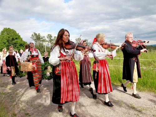 Musiker i traditionella folkdräkter bjuder in till dans i Sijansnäs.